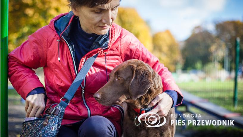 Kobieta w czerwonej kurtce nagradza przysmakami swojego psa