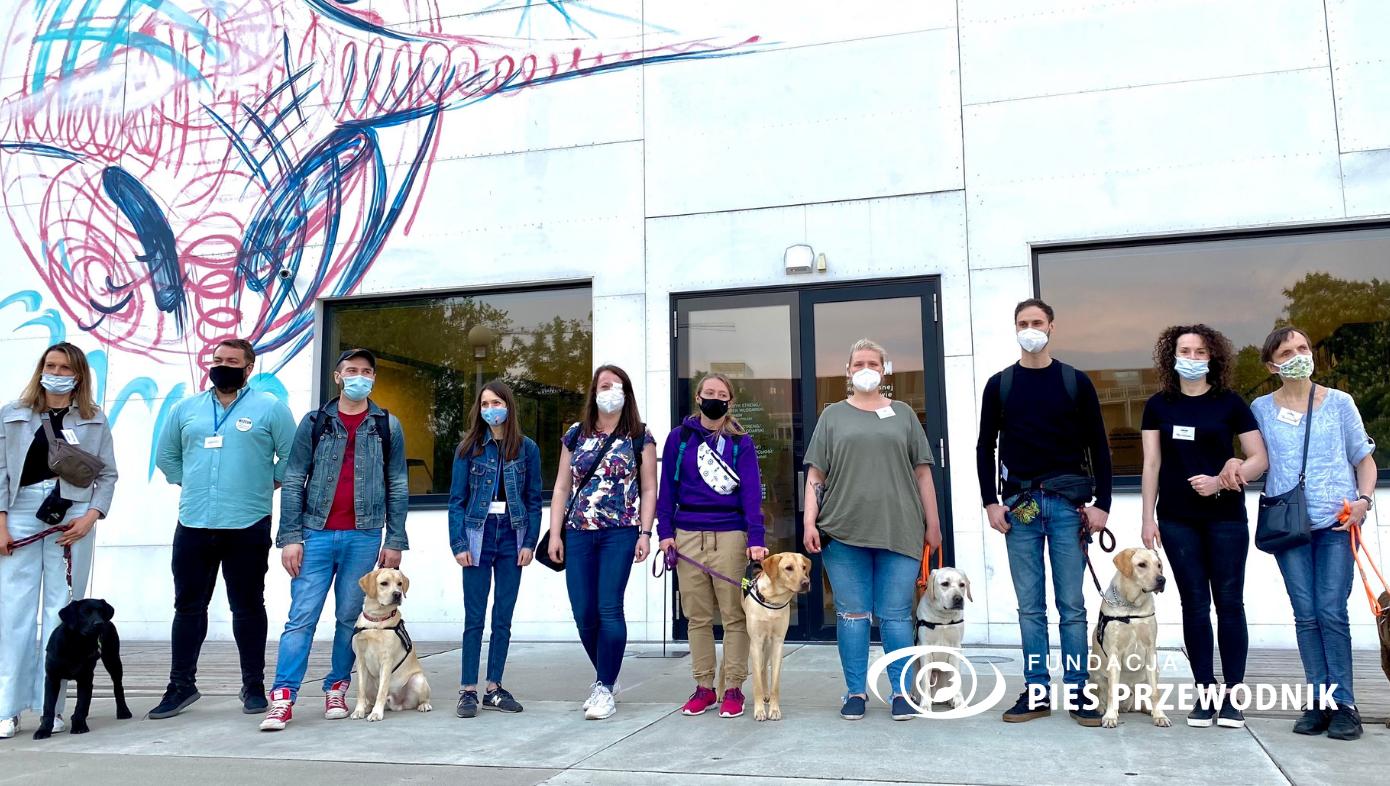 Przed wejściem do muzeum stoi grupa wolontariuszy z psimi adeptami