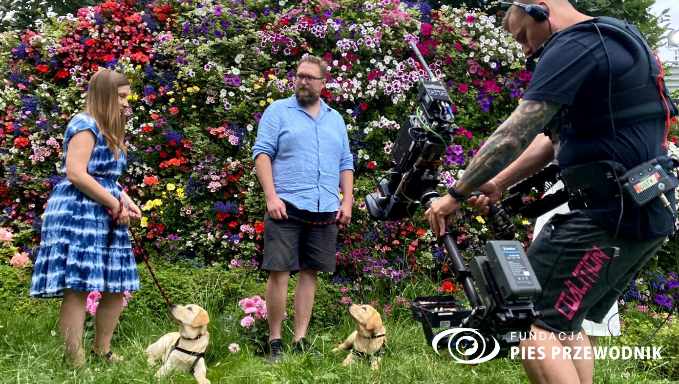 Podczas prezentacji pogody przed ścianką pełną kwiatów stoi dwójka wolontariuszy z dwoma szczeniaczkami